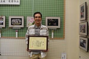 最優秀賞の作品展示(右)で笑顔を見せる佐藤さん