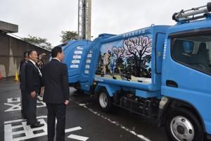 ボディプリントされた車両を見る香川武文市長ら(17日の車両発表会で)