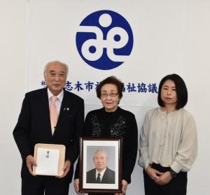遺贈を受けた谷合会長(左)と横山さんの遺影を手にする三村さんと親族(右)